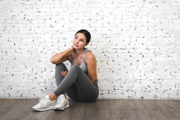 Спортивная женщина в спортивной одежде расслабиться после тренировки против копирования пространство для добавления текста с белой стеной. концепция диеты. фитнес и здоровый образ жизни