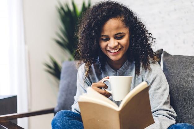 ホットコーヒーのカップをリラックスして読んで若いアフリカ系アメリカ人女性