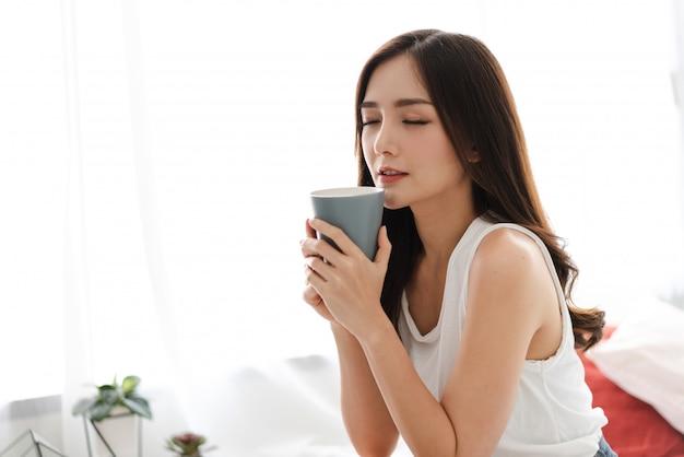 朝の寝室でコーヒーを飲む女性