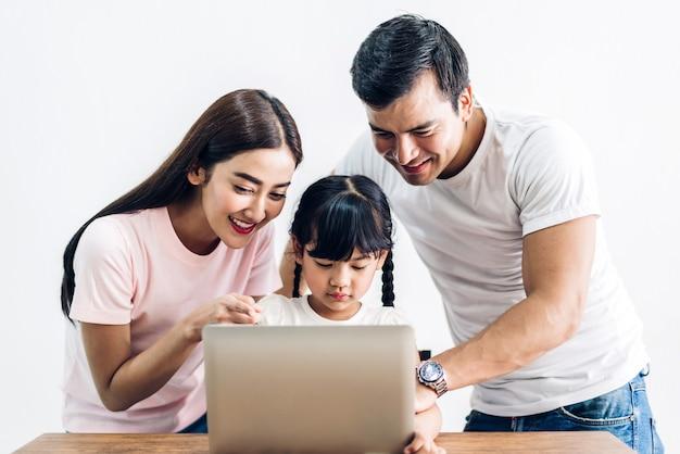 幸せな家族の父と娘が座っていると自宅のリビングルームで一緒にラップトップコンピューターを見て母