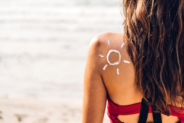 Женщина в бикини, применяя крем с солнцем на спине