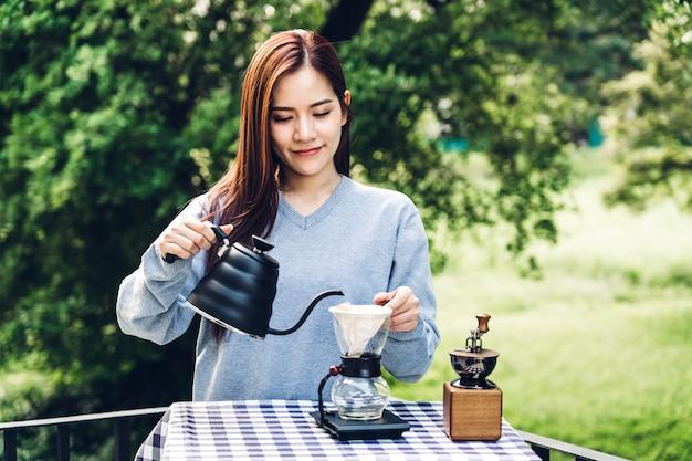 公園でドリップコーヒーを作る女性バリスタ