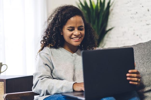 Молодая афро-американская чернокожая женщина ослабляя и используя портативный компьютер. женщина, проверка социальных приложений и работы. концепция коммуникаций и технологий
