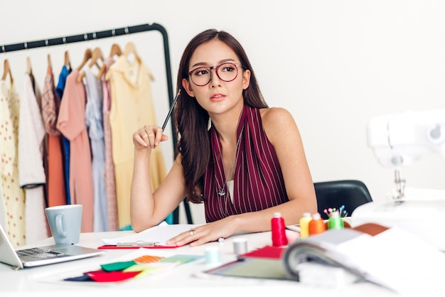 Усмехаясь модельер женщины азии работая с портативным компьютером на студии мастерской