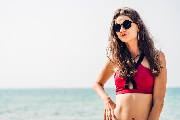 Портрет улыбается женщина релаксации в красном бикини на тропическом пляже. летние каникулы