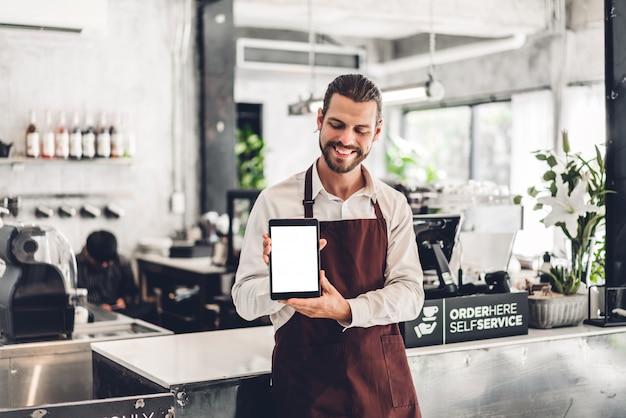 カフェでモックアップが空白のタブレットコンピューターやカフェのコーヒーショップで立っているバリスタ男中小企業経営者の肖像画