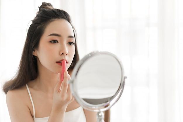 鏡で見ていると、自宅で赤い口紅を適用することを楽しんでいる笑顔の美しい女性の新鮮な健康的な肌。顔の美しさと化粧品のコンセプト