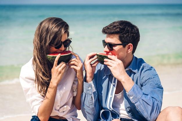 ロマンチックな恋人の若いカップルが熱帯のビーチでスイカのスライスを保持して食べてリラックスします。夏の休暇