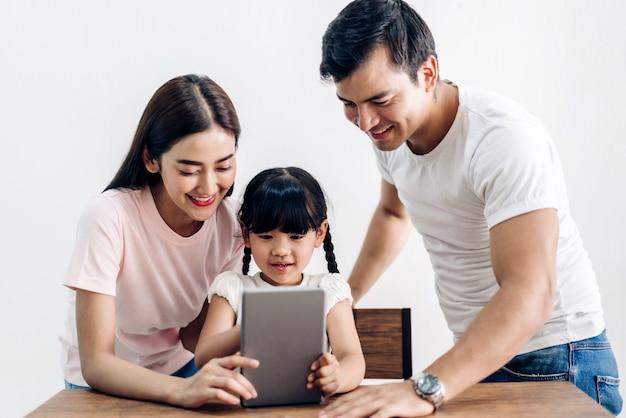 幸せな家族の父と娘が座っていると自宅のリビングルームで一緒にタブレットコンピューターを見て母