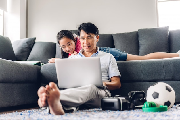 Усмехаясь азиатский человек ослабляя используя болтовню встречи работы компьютера и видео-конференции портативного компьютера при его дочь дочери уча книгу чтения и изучая знание на дому. работа от концепции дома