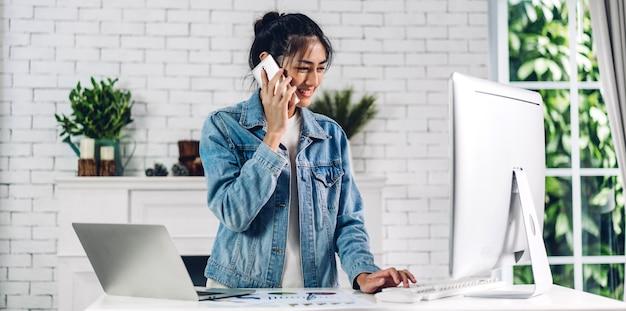 Молодая усмехаясь счастливая азиатская женщина ослабляя используя настольный компьютер работая и видеоконференция встречая онлайн-чат дома. творческий смартфон пользы девушки и печатать на клавишах