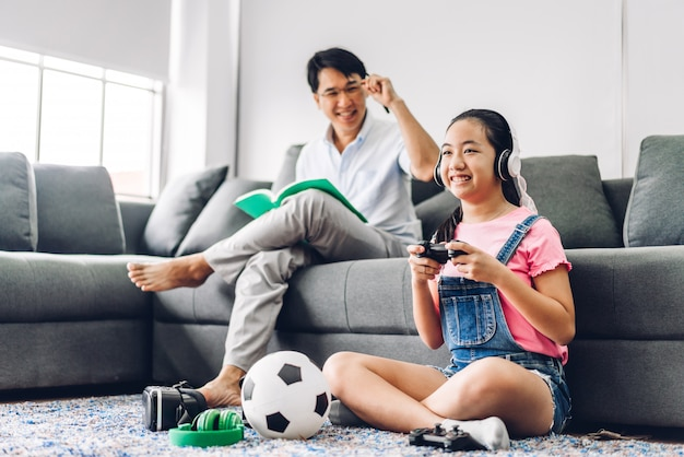 Оягнитесь маленькая азиатская девушка имея потеху наслаждаясь видеоигрой консоли игры с отцом пока сидящ на кресле дома