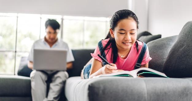 Школьница маленькая девочка учится и делает домашнее задание, изучая знания по книге с отцом, отдыхая с помощью ноутбука и видеоконференцсвязи в чате на дому. работа из дома концепции