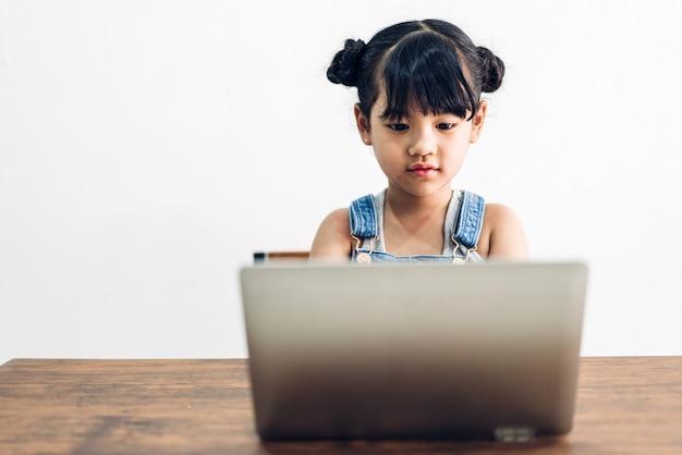 Школа маленькая девочка учится и сидит, глядя на портативный компьютер