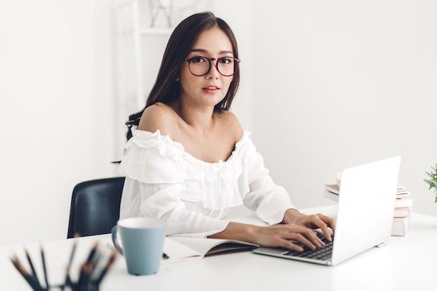 Студент девушка сидя и изучая и уча онлайн с портативным компьютером и читая книгу перед экзаменом на дому. концепция образования