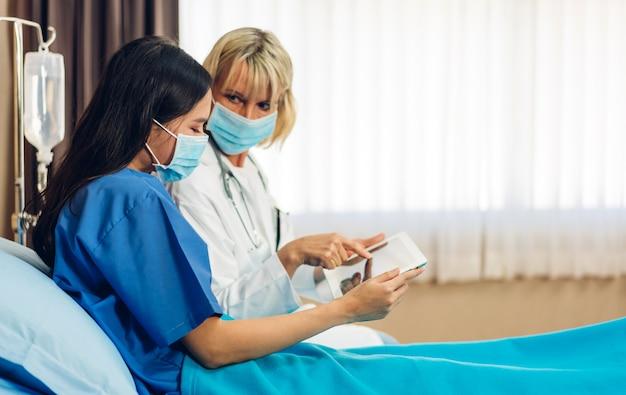 病院でマスクを着ている患者と話している女性の医者