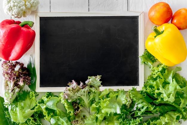 Здоровые овощи и черная доска на деревянном фоне