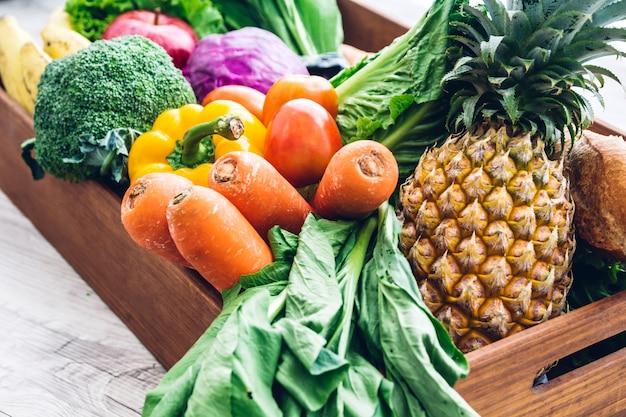 白い木製のテーブルの上に異なる新鮮な果物や野菜