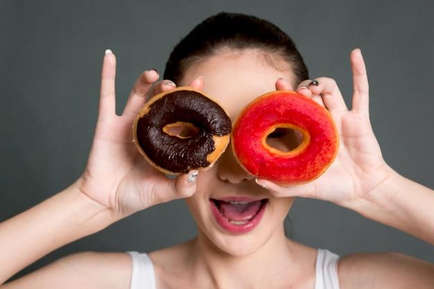 灰色の背景にカロリー爆弾ドーナツを握っている女性