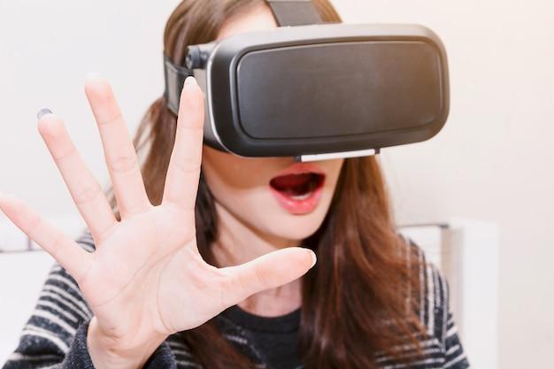 Молодая женщина наслаждаться с виртуальной реальности очки у себя дома