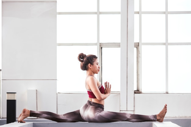 大きな窓の前でヨガを練習している女性