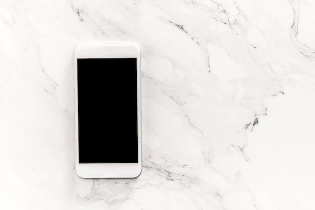 白い大理石の背景に空白の画面を持つモックアップスマートフォンの平面図です。