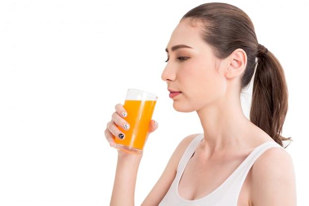 白い背景で隔離のオレンジジュースを保持している女性