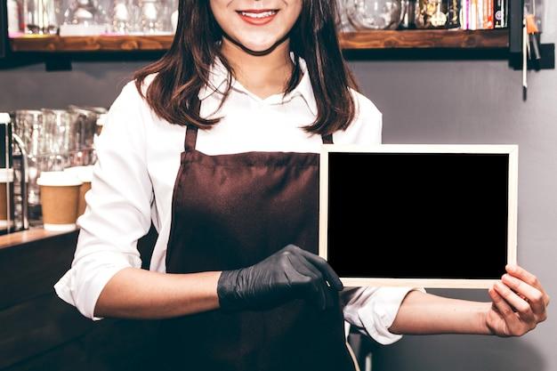 Бариста держит доску в кафе-ресторане