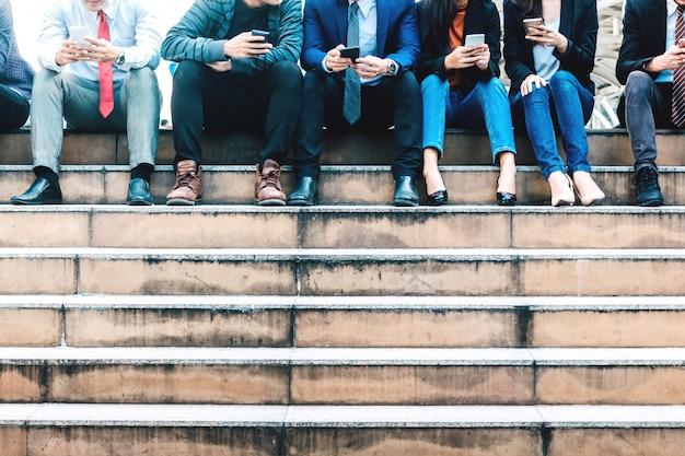ビジネスマンのグループがスマートフォンの技術を一緒に利用している