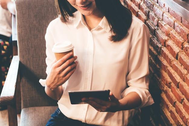 Женщина пьет кофе и работает на планшете в кафе