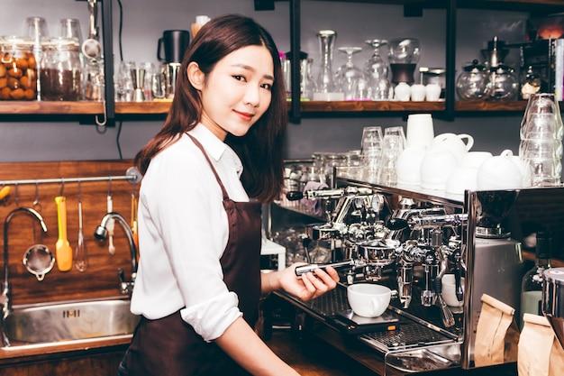 Женщины бариста используют кофемашину для приготовления кофе в кафе
