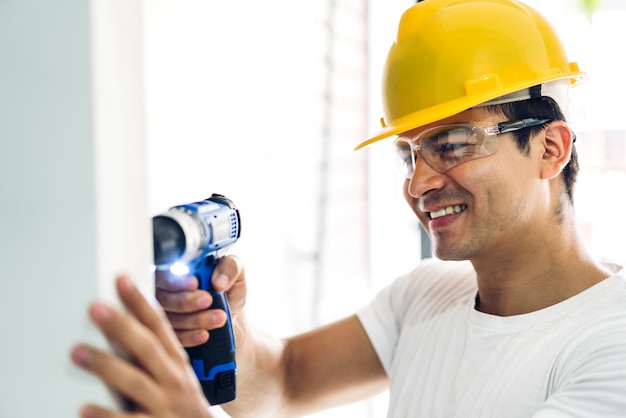Молодой строитель работает с отверткой, чтобы сверлить в подъезде дома