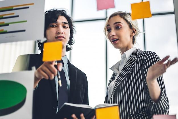 カジュアルなビジネス人々の計画とブレーンストーミングのグループは、近代的なオフィスのガラス窓にステッカーノートとプロジェクトを書きます。チームワークの概念
