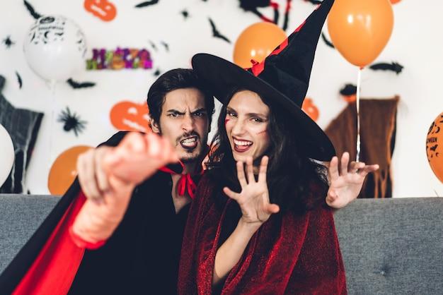 楽しんでいるカップルが身に着けているカーニバルのハロウィーンの衣装とハロウィーンパーティーで背景にコウモリと風船でポーズメイク。ハロウィーンの休日のお祝いのコンセプト