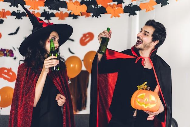 カボチャを押しながらカーニバルのハロウィーンの衣装を着て楽しんでカップル