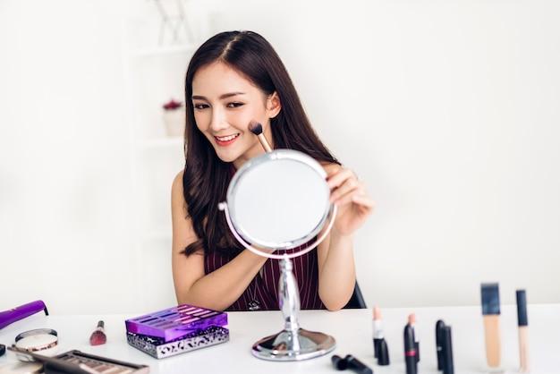 Усмехаясь кожа молодой красивой азиатской женщины свежая здоровая смотря на зеркале и держа щетки состава с косметиками установленными на дом. лицевая концепция красоты и косметики