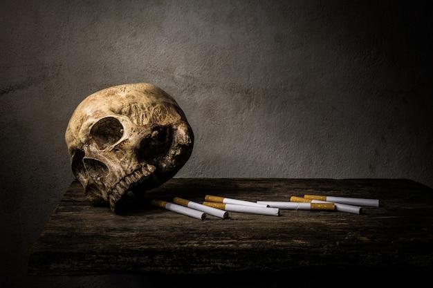 Натюрморт с черепом и сигаретой люди курят сигарету и получают токсин