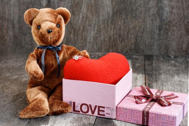 おもちゃのクマの人形と赤いハートのジュエリーリング。