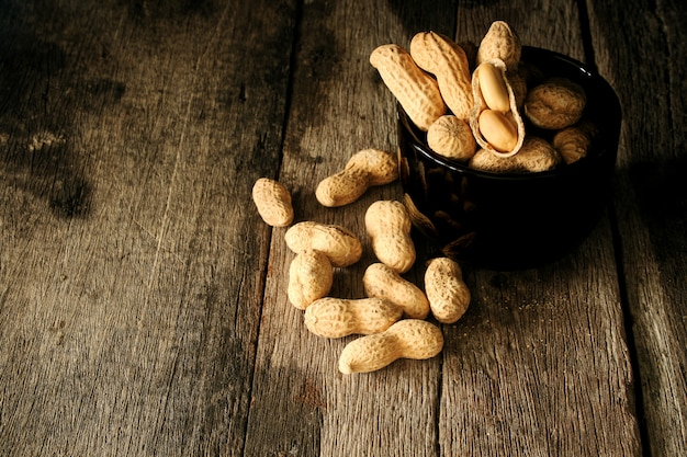 Оболочка арахиса натюрморта открытая для того чтобы показать семя в стороне на деревянном