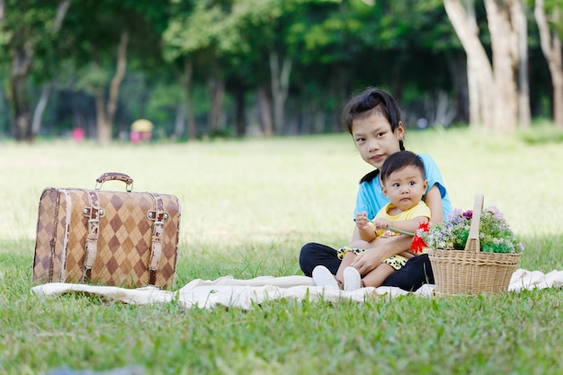 Портрет очаровательны брат и сестра улыбаться и обниматься, сидя в парке.