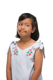 かわいいアジアの暗い女の子が顔に面白い感情を作ります。