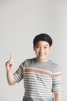 アジアの少年の思考とコピースペースに笑みを浮かべて指しています。