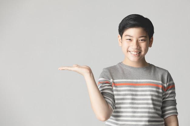 Молодой азиатский мальчик думая и показывая пока усмехающся с космосом экземпляра.