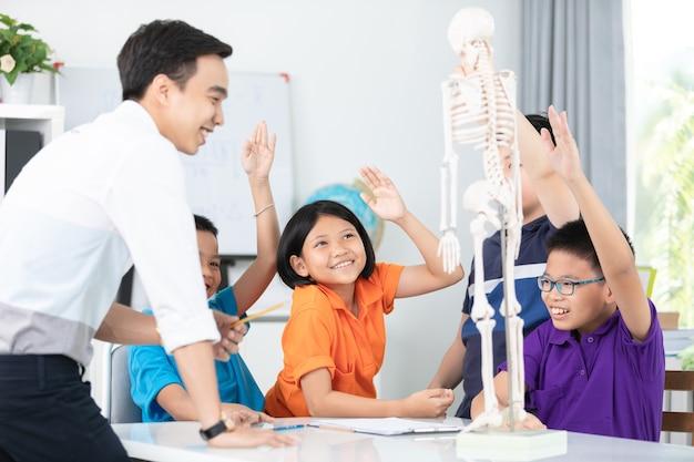 アジアの先生が人の体の構造を少人数に説明