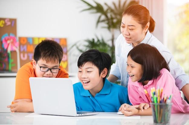 Учитель и симпатичные азиатские дети, используя ноутбук вместе.