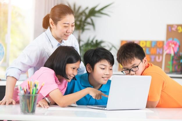 教師とかわいいアジアの子供たちが一緒にラップトップコンピュータを使用しています。
