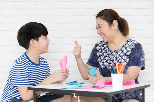 母親の家庭であなたの宿題を教えて学ぶアジアの少年
