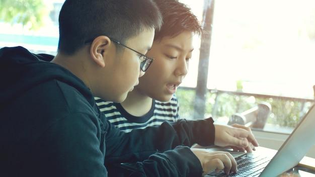 ラップトップコンピュータでタイピングしている幸せなアジアの少年。