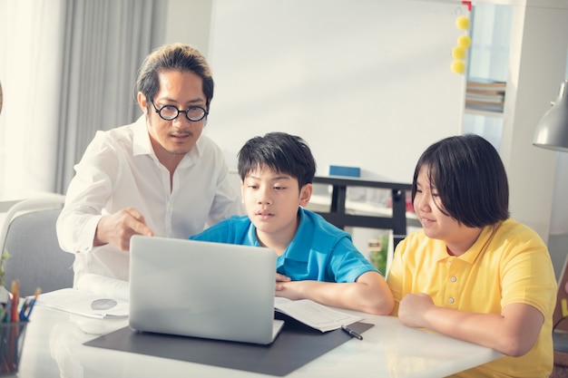 ラップトップコンピューターで学習クラスの家庭教師室の子供たち