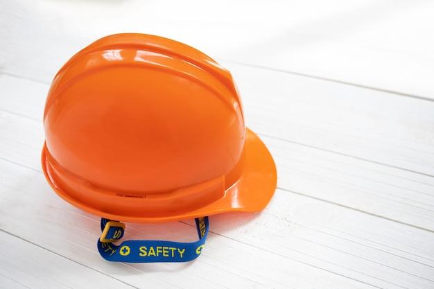 白い木製の背景にエンジニアまたは職長の安全ヘルメット。